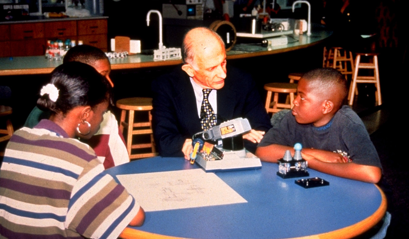 Jerome Lemelson sitting at a round table in the former Hands On Science Center, with three tweens, discussing invention.