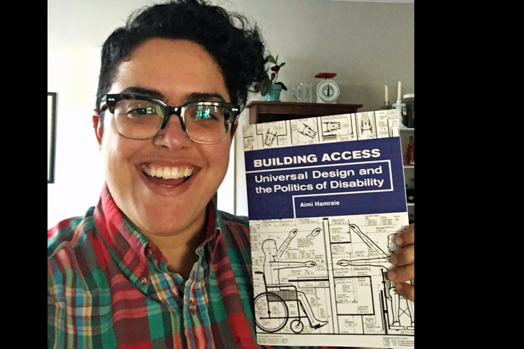 Informal portrait photo of Aimi Hamraie holding her book Building Access