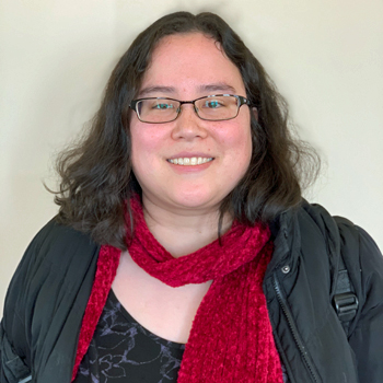 Elizabeth Badger, wearing a bright red scarf, photographed against a beige background