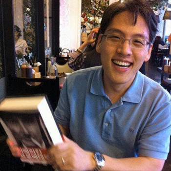 Hyungsub Choi holding a book and smiling broadly