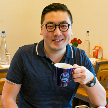 "William Chou, holding a coffee cup that reads ""Petit Chou"""
