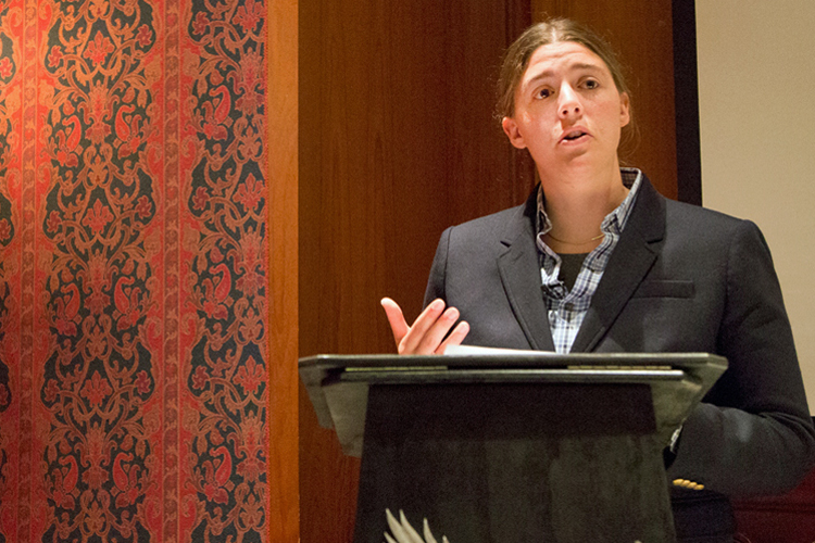 Rachel Gross standing at a podium, presenting a talk about her research, 2014