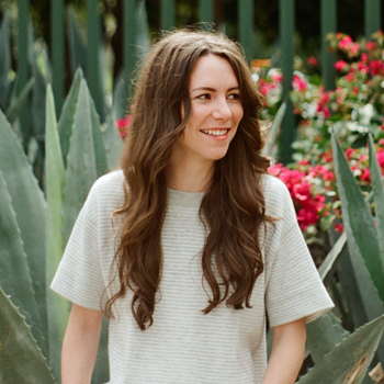 Three-quarters candid photo of Samantha Shorey, photographed against a lush setting of agave and bougainvillea plants. She wears an off-white short-sleeve top. She is looking to the right at something not visible in the image.
