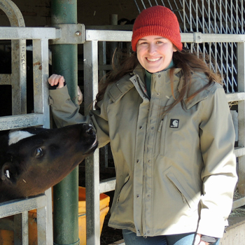 Nicole Welk-Joerger was photographed at a cow pen. She is wearing a red knit cap, and heavy gray jacket, and blue jeans. A cow is poking its head between the rails of the pen, reaching out to Welk-Joeger.