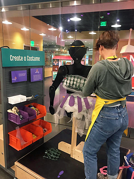 "Hannah Correlli, a young woman with short, dark hair and wearing jeans, a hoodie, and a yellow SparkLab apron, stands with her back to the camera, working on an articulated human cutout form in the ""Create a Costume"" activity in SparkLab."