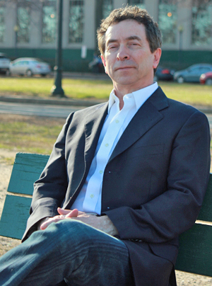 Christopher Weaver sitting on park bench on Memorial Drive in Cambridge, Mass.