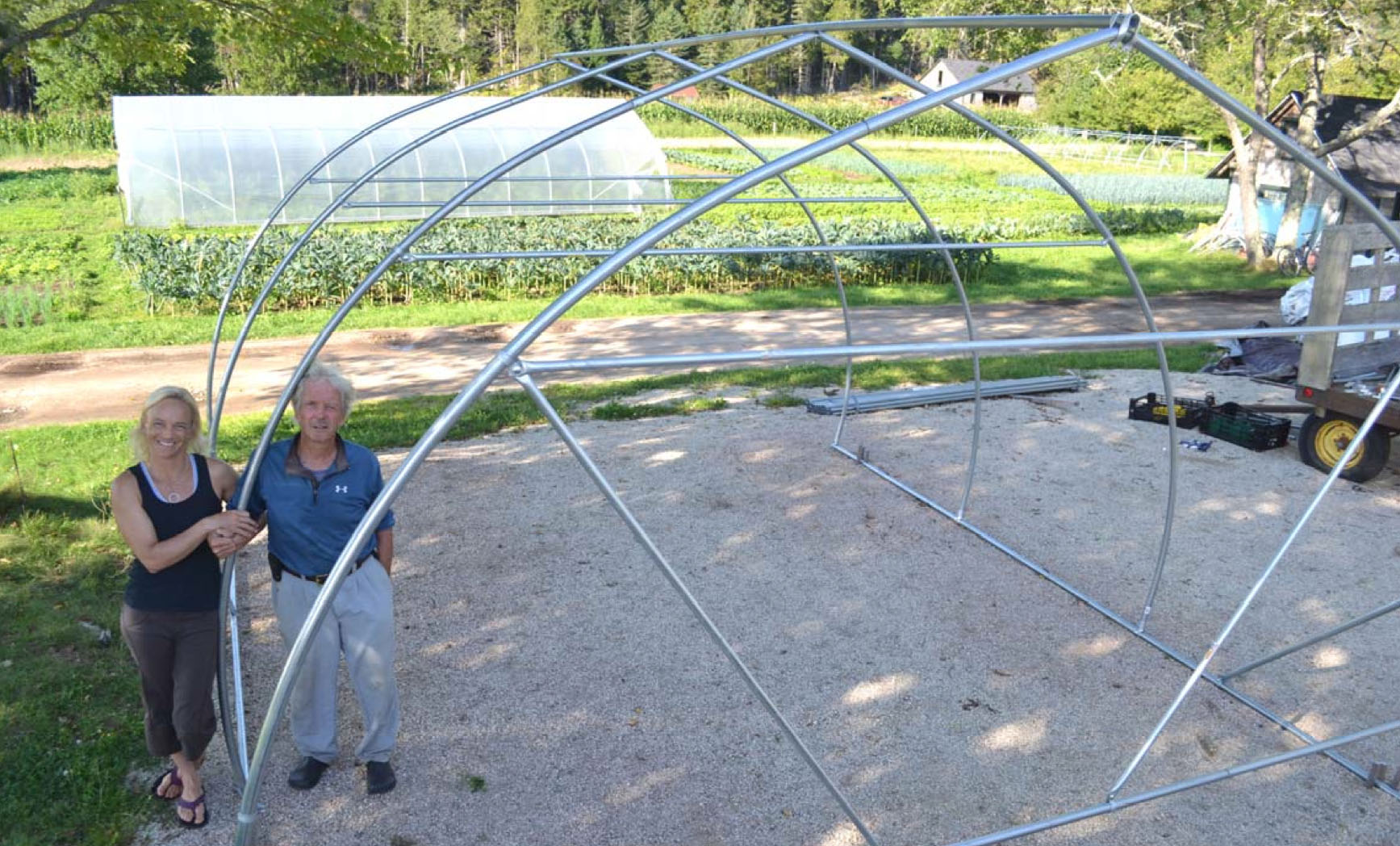Eliot Coleman poses with his daughter Clara Coleman at Four Season Farm in Harborside, Maine. The two have just completed framing part of the 14' Gothic Modular Moveable Tunnel, based on Mr. Coleman's designs.