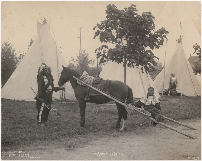Archival photo of a Native American using a travois.