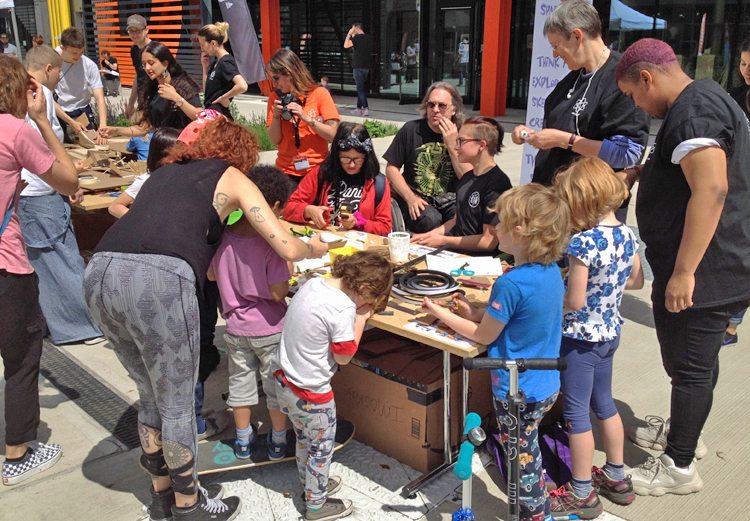 Groups of kids and their adults work at hands on projects at an outdoor table.