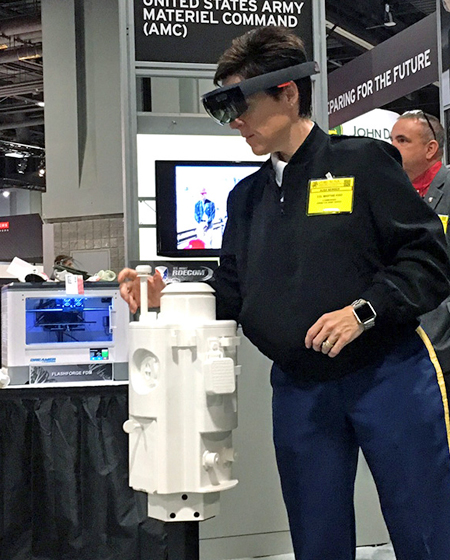 Servicewoman trying out augmented reality with Hololens in a trade fair setting