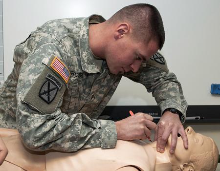 Medic practicing on a medical training manikin