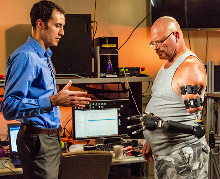Engineer with soldier testing modular prosthetic arm