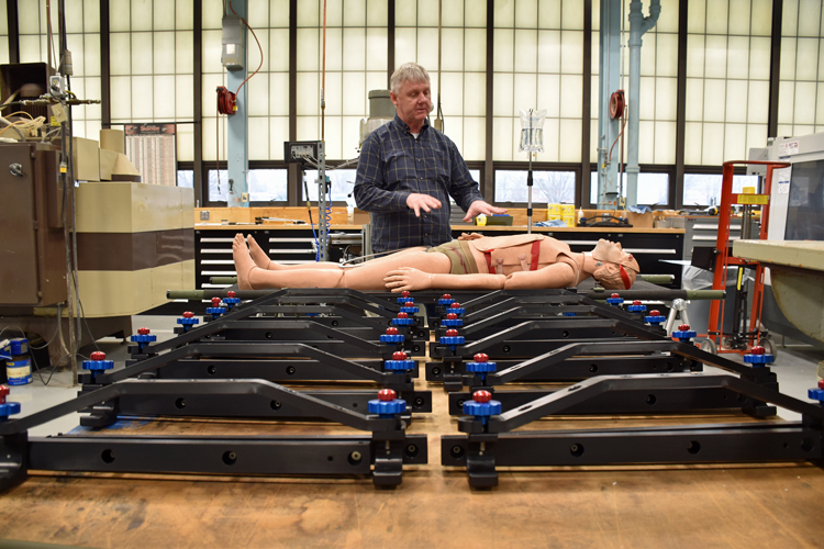 A man points to a mannequin simulating a medical patient lying on a stretcher. A rail, called the SHRAIL, is attached to the side of the stretcher and holds an IV bag. Several more unattached SHRAILs fill the foreground.