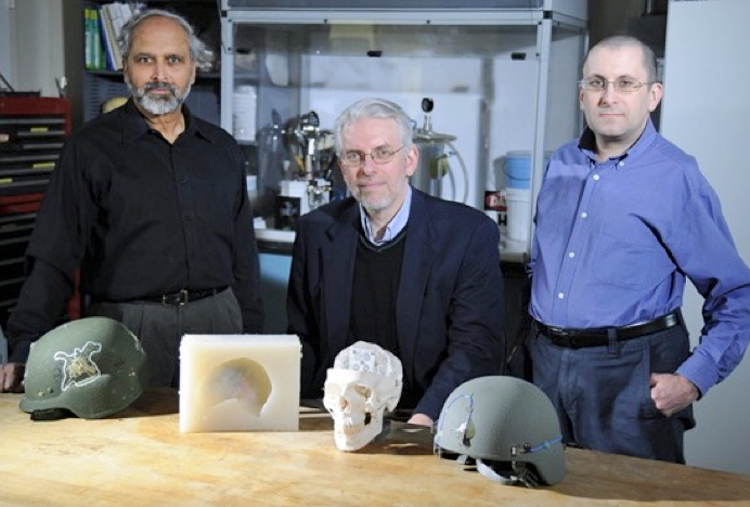 Three scientists posing with GelMan synthetic substitutes for live animals or clay materials used in testing new body armor, helmets, and flak jackets. A mold, partial skull, and 2 helmets are on the table in front of the scientists.