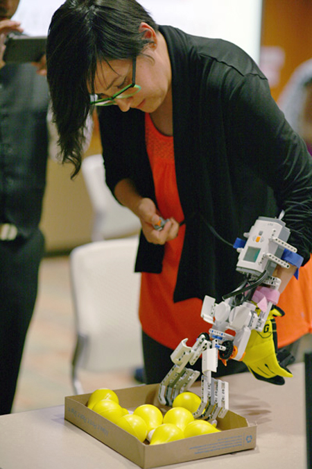 A woman bends over a box of yellow balls, trying to pick one up using the robotic hand that is attached to her arm.