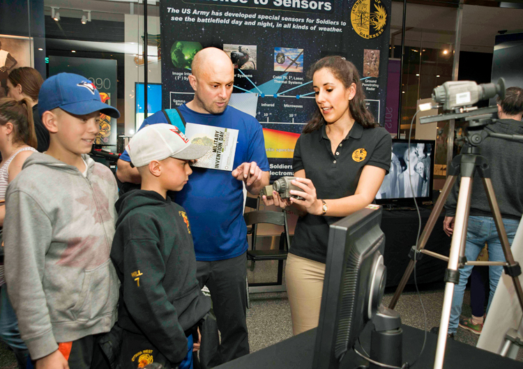 Two children and an adult look at a night vision lens while in conversation with a woman engineer from the Army Night Vision and Electronic Sensors Directorate. A poster in the background has information about the history and current applications of night vision electronics.