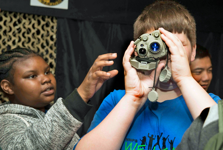 Two pre-teens, one of whom is looking through a night vision scope, while the other is reaching for the scope.
