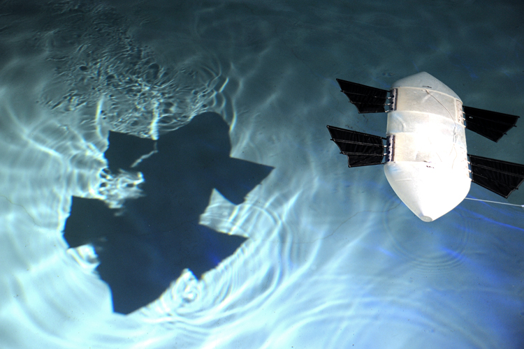 A rectangular swimming drone in a pool of water casts its shadow on the pool's bottom. The drone has two sets of fins on each side and can move quickly through the water.