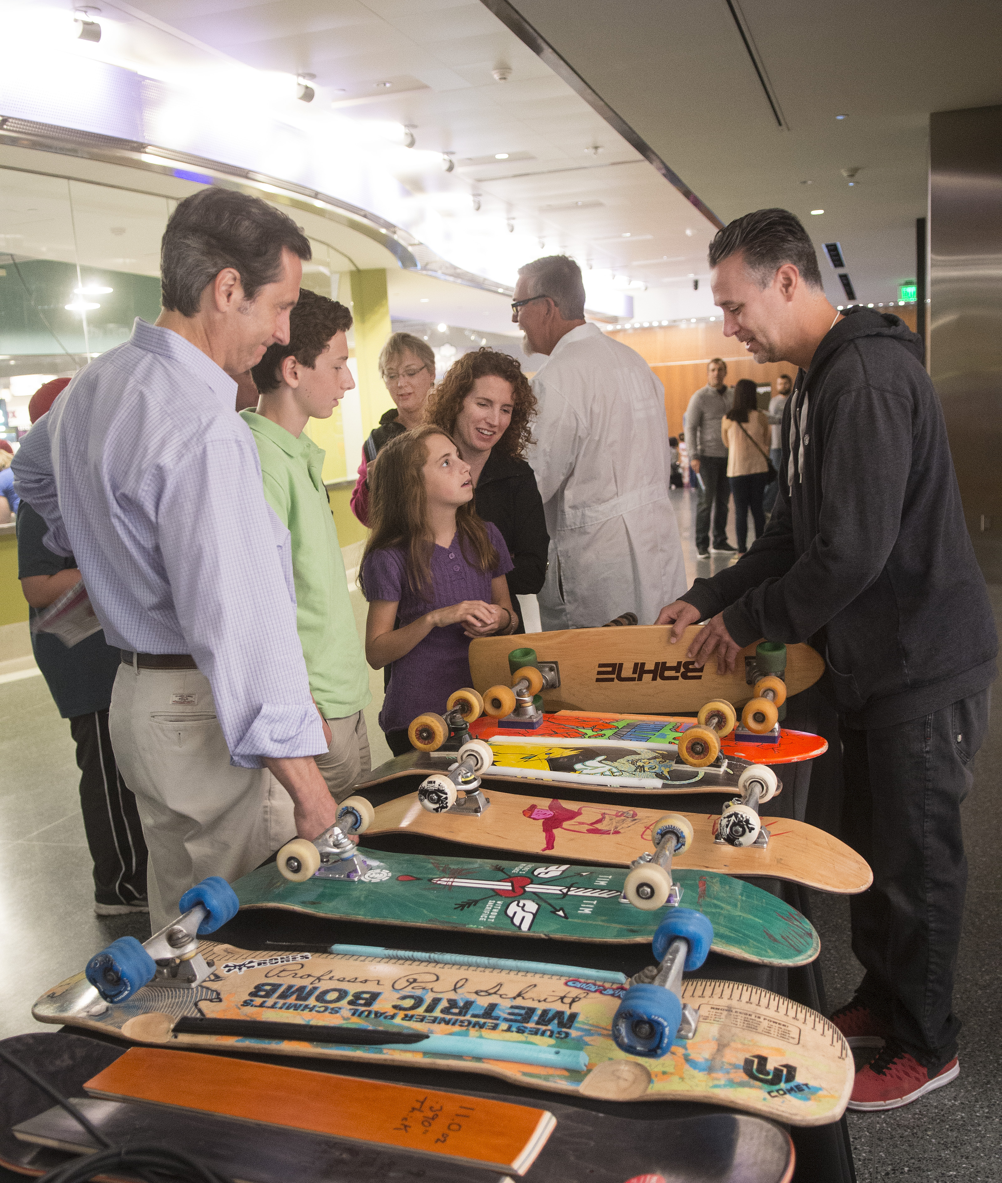 Josh Friedberg demonstrates historic skateboards to visitors to the Innoskate table at the USPTO/Smithsonian Innovation Festival