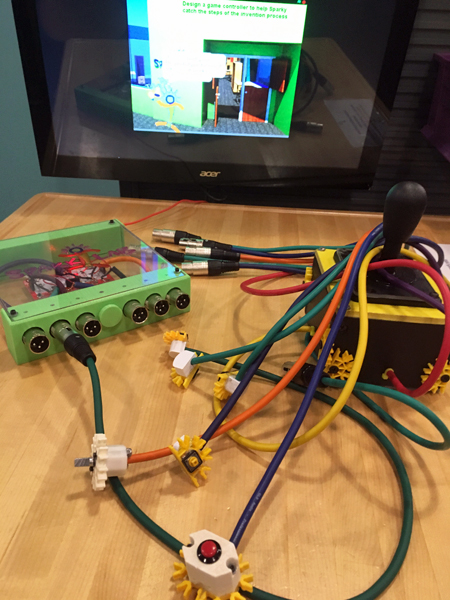 "A tangle of purple, green, yellow, orange, and red cables with 3-prong connectors are arrayed on a table. A green cable is connected to a box of circuitry with a clear top and a green metal frame. Several cables wrap around a joystick; a red cable comes out of the joystick base. A computer screen at the end of the image displays a graphic of Sparky outside of SparkLab and the text ""Design a game controller to help Sparky catch the steps of the invention process."""