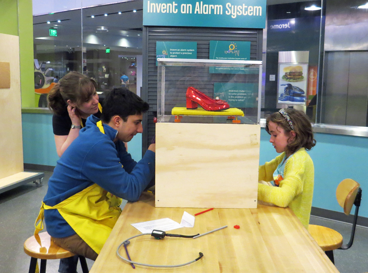 SparkLab facilitators work with a young girl on an alarm for the ruby slippers