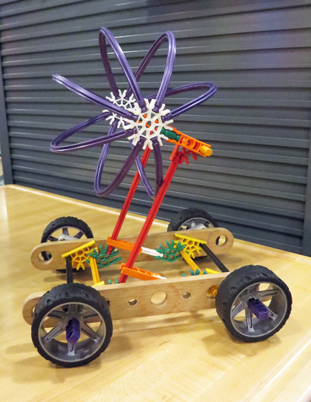 A child has built a model for his or her idea for a nuclear-powered car, using plastic wheels, wooden rails, plastic gears, and flexible plastic sticks. The top of the car looks like the symbol for nuclear power.