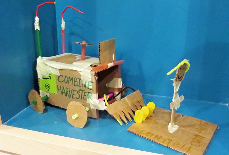 A cardboard combine harvester, complete with a farmer stick figure and cardboard corn field.