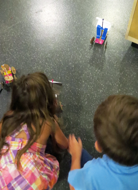 A young girl and boy are sitting on the floor, testing their inventions of vehicles with wheels and sails. The little girl seems to be blowing into the paper sail of one vehicle.