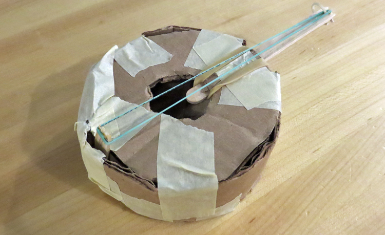 Banjo-like instrument made of cardboard, tape, and string