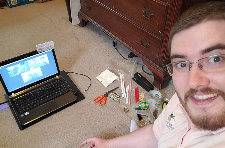 Zach Etsch sitting on the floor with his laptop and an array of craft supplies