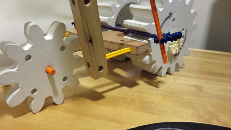3 wooden gear-shaped wheels and wooden members with holes drilled in them are connected with Knex to form a 3-wheeled vehicle.
