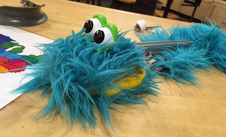 A muppet-like toy made of blue fake fur with big googly eyes