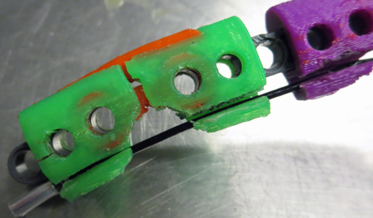 2 green and 1 purple rectangular plastic pieces, each with 2 holes side-by-side, are attached to a metal support. The pieces at the left also has pins that fit into its holes.