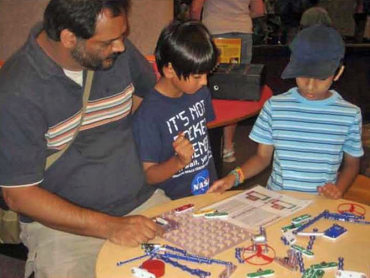 An adult man and two young boys working at a table on a snap circuits activity in Spark!Lab.