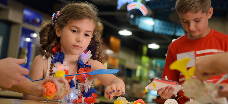 A young girl and boy working on a SparkLab activitiy
