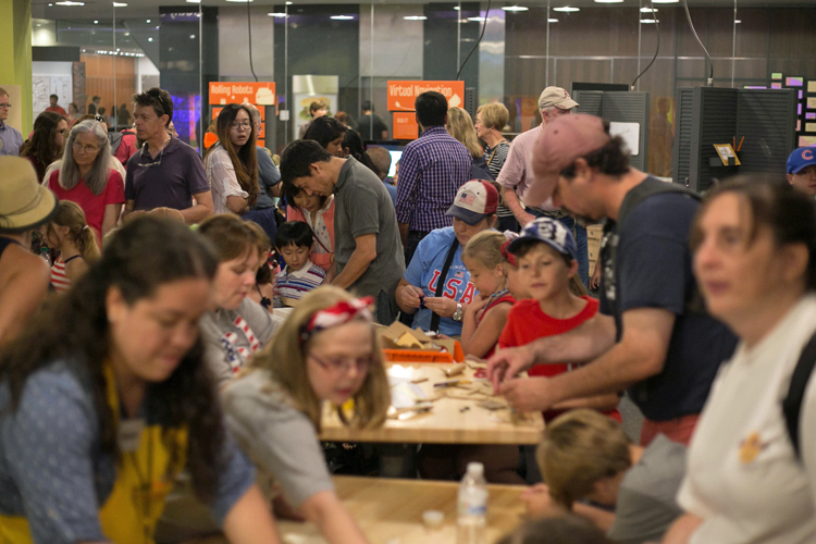 In the large main space of SparkLab, many, many children and adults are working on activities, talking, observing, and interacting with SparkLab staff. Two long tables covered with craft materials are visible, with children and their accompanying adults creating inventions. The photo was taken during the grand reopening of SparkLab in July 2015.