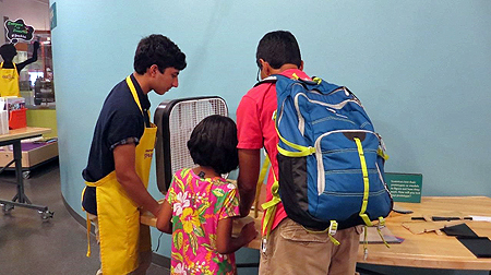 A teenage male wearing a bright yellow apron, a grown-up male, and small child are looking at a table with wooden and plastic materials on it. Their backs are toward the viewer and what they are looking at is out of sight.