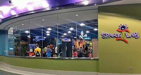 A lime green wall with the Spark!Lab logo on the right side. To the left of the wall with the logo is a long, curved wall of clear glass windows to see inside the Spark!Lab space.