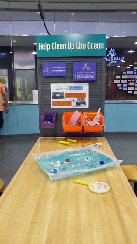 A Spark!Lab activity station. A picture of an activity station, taken from the front view. In the middle of the picture is a light wooden table. teal title panel says Help Clean Up the Ocean.