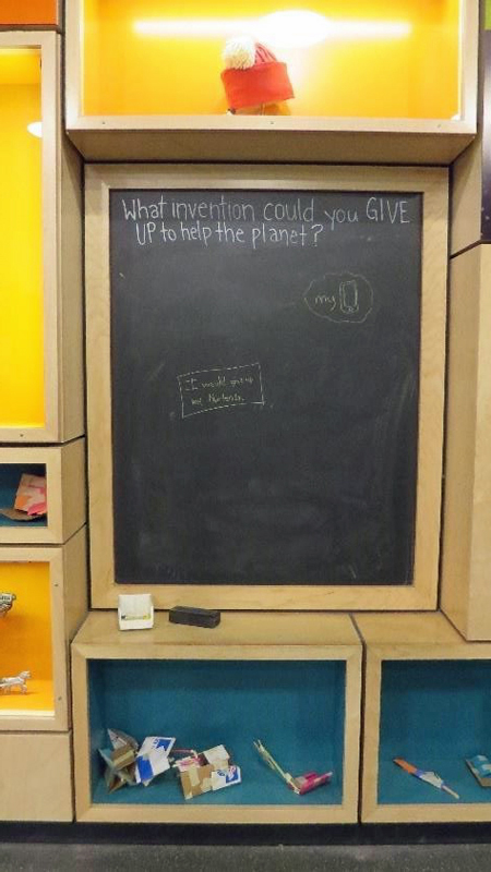 Chalkboard and light wood cabinets and cubbies that have orange or blue interiors and objects on display in lighted glass cases. Below the cubbies and cabinets is a large square blackboard and a wooden shelf underneath with more cabinets and drawers.