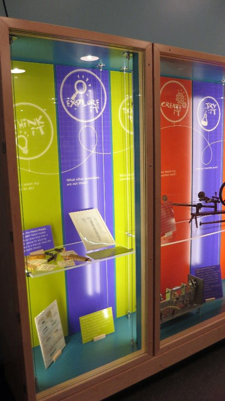 A light wooden display case with a glass cover and glass shelves holds objects, books, and papers. At the back of the display case are colorful  panels with logos that say think it, explore it, create it, and try it.