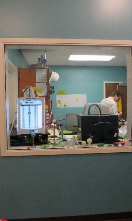 A blue wall with a clear window in the middle. Looking through the window you can see Inventor Tim and his workshop filled with tools, 3D printers on a workbench, an orange cabinet, and pieces of paper hanging on the walls.