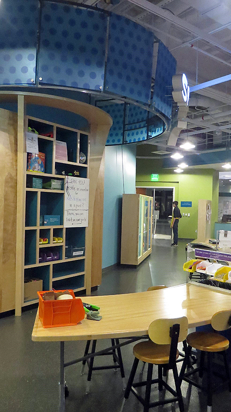 Sparklab interior taken from the back of the room. In the foreground a light wooden curved table with stools and some craft supplies in an orange bucket. Behind the table is are light wooden shelves with buckets of materials.