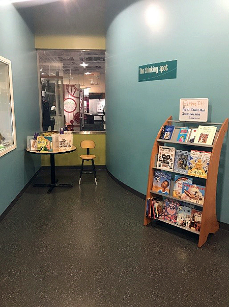 On the wall, a sign says Thinking Spot. Under the sign is a wooden book shelf with four shelves displaying childrens books. In the background is a round table with more childrens books on display.