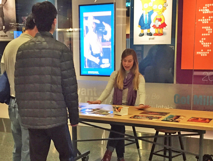 Two visitors engage with museum faciliator at a matching game outside American Enterprise!