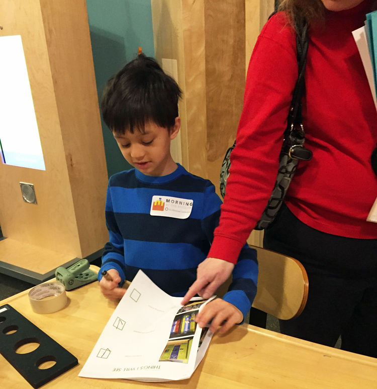 A young boy is working with the social narrative and checklist
