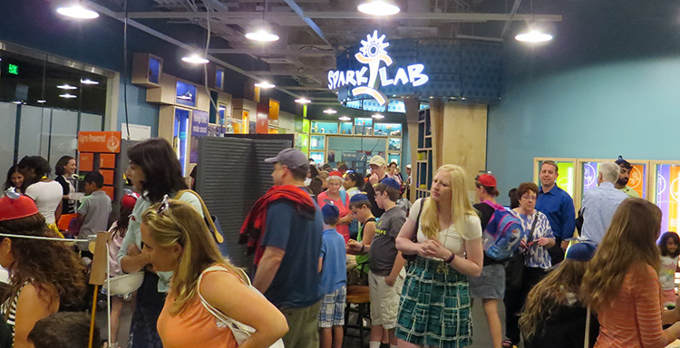 A large crowd of adults and kids in SparkLab