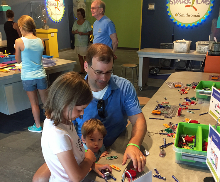 A father and two children work on an activity at SparkLab in Fort Myers