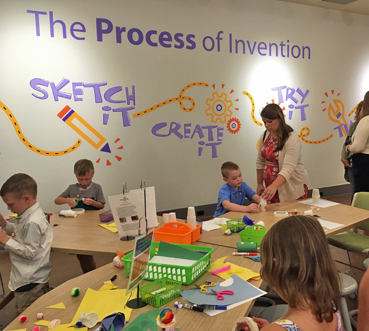 "3 young boys and 1 young girl work at activity tables, using craft materials in front of them. An adult woman assists 1 boy. ""The Process of Invention"" is written in large letters on the wall, along with the illustrated words Sketch It! Create It! Try It!"