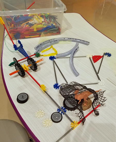 A table covered with plastic pieces of different shapes used to create a net to catch a plastic dinosaur.